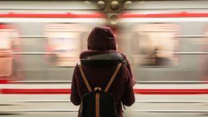 Frau einsam vor einem fahrenden Zug